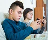Moder och son med hemmastadda smartphones Arkivfoto