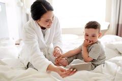 Moder och son med smartphonen i säng på hotellet Royaltyfri Foto