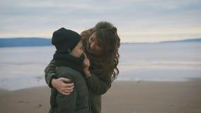 Moder och son på stranden Kvinna som kramar hennes barn Ett barn är i ett utmärkt lynne medföljer hans moder dem arkivfilmer
