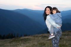 Moder och son på ryggen i bergen Arkivfoto
