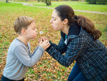 Moder och son som blåser maskrosen Royaltyfria Bilder