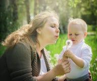Moder och son som blåser på en maskros Arkivfoto