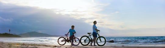 Moder och son som cyklar på stranden arkivbild