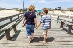 Moder och son som går handen - in - hand arkivfoto