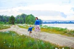 Moder och son som går på landsvägen Fotografering för Bildbyråer