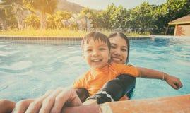 Moder och son som har gyckel i en simbassäng Arkivbild