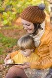 Moder och son som har gyckel med en minnestavlaPC Arkivfoto