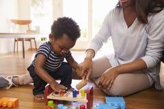 Moder och son som hemma spelar med leksaker på golv Royaltyfria Foton