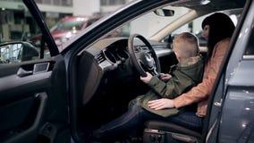 Moder och son som kontrollerar inre av den nya bilen lager videofilmer