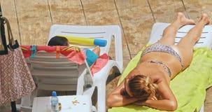 Moder och son som kopplar av på sunbed nära pöl på semesterorten lager videofilmer