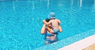 Moder och son som kopplar av på sunbed nära pöl på semesterorten stock video