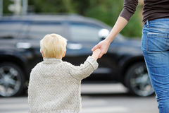 Moder och son som korsar gatan på övergångsstället Royaltyfria Foton