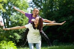 Moder och son som låtsar för att flyga Royaltyfria Foton