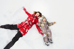 Moder och son som ligger i snön Royaltyfri Bild