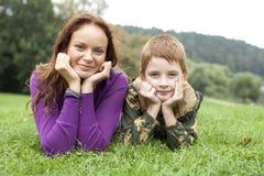 Moder och son som ligger på det gröna gräset Arkivbilder