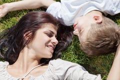 Moder och son som ligger på gräshuvudet - - huvud Arkivbild