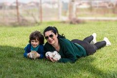 Moder och son som rymmer små kaniner royaltyfri fotografi