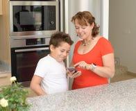 Moder och son som söker efter ett recept i mobiltelefonen royaltyfri foto