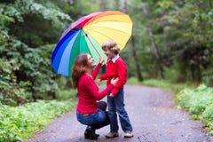 Moder och son som skrattar under ett färgrikt paraply Arkivfoto