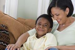 Moder och son som smyga sig på soffan Royaltyfri Foto