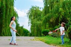 Moder och son som spelar badminton i parkera arkivfoton