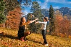 Moder och son som spelar i höst Royaltyfria Bilder