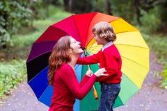 Moder och son som spelar under ett färgrikt paraply Arkivbilder