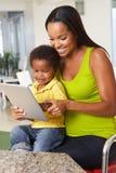 Moder och son som tillsammans använder den Digital minnestavlan i kök Royaltyfri Foto
