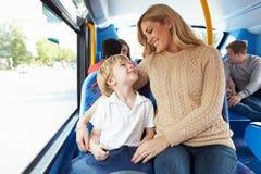 Moder och son som tillsammans går till skolan på bussen Royaltyfri Bild