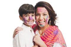 Moder och son som tycker om holi fotografering för bildbyråer