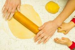 Moder- och sonhänder som knådar deg på tabellen Arkivfoto