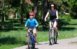 Moder- och sonridningen cyklar utomhus i sommar Royaltyfri Fotografi