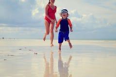 Moder- och sonspring i vatten på stranden Arkivfoto
