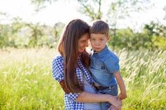 Moder- och sonstående mot den gröna trädfamiljen royaltyfri bild