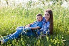 Moder- och sonstående mot den gröna trädfamiljen royaltyfri fotografi