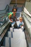 Moder- och sonturister går på rulltrappan arkivbild