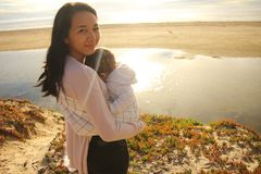Moder och sovabarn på en strand Royaltyfri Bild