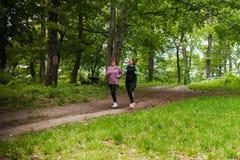 Moder och sportswear och spring för dotter bärande i skog på Fotografering för Bildbyråer