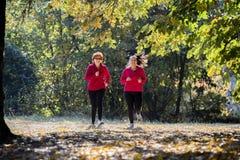 Moder och sportswear och spring för dotter bärande i skog arkivbilder