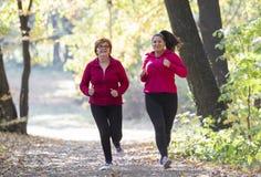Moder och sportswear och spring för dotter bärande i skog arkivfoto