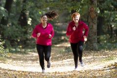 Moder och sportswear och spring för dotter bärande i skog arkivbild