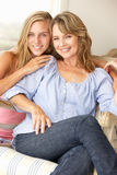 Moder och tonårs- dotter på ome på sofaen Royaltyfri Bild