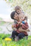 Moder och två barn som beundrar vårträdgården Royaltyfri Bild
