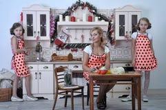 Moder och två döttrar i köket royaltyfria foton