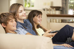 Moder och två barn som tillsammans sitter på Sofa At Home Watching TV Arkivfoton