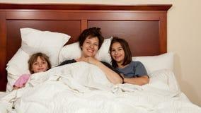 Moder och två döttrar i säng Arkivfoton