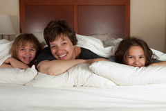 Moder och två döttrar i säng Royaltyfri Foto