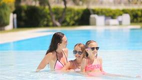 Moder och tv? ungar som tycker om sommarsemester i lyxig simbass?ng stock video