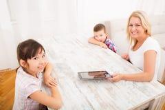 Moder och ungar med en minnestavlaPC Arkivfoto