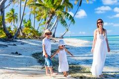 Moder och ungar på en tropisk strand Royaltyfria Bilder